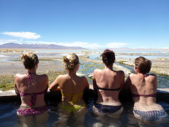 Natural hot spring overlooking a lake rimmed with volcanoes in Bolivia