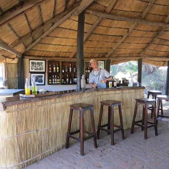 Mike Howard tending bar at Robin Pope's Nsefu Camp