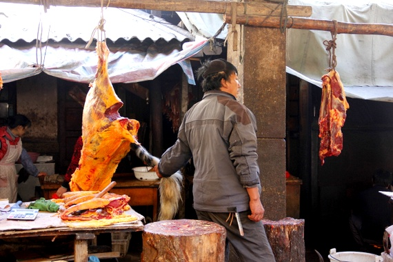 Chinese butcher holding a tail